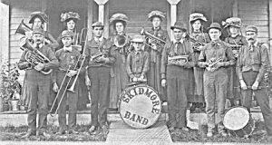 "Photograph of the members of the Skidmore, Missouri town band.  One member poses by a large bass drum emblazoned with the words ""Skidmore, Missouri."""