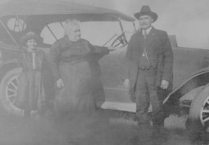 A young girl, older woman, and man stand in front of an early-model automobile.  The photo has been identified as being of Violet Lent and Lydia and Gaylord Dilts.