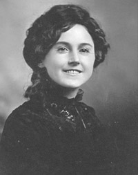 Antique photograph of a pretty woman.  She is wearing a high-necked dark blouse and has her dark hair up.  She is smiling.
