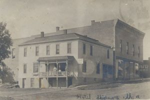 "Antique photo image of two buildings. The smaller building has a sign which reads, ""The New Commercial Hotel."""