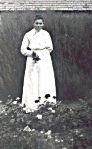 A woman in a white dress stands behind some flowers.